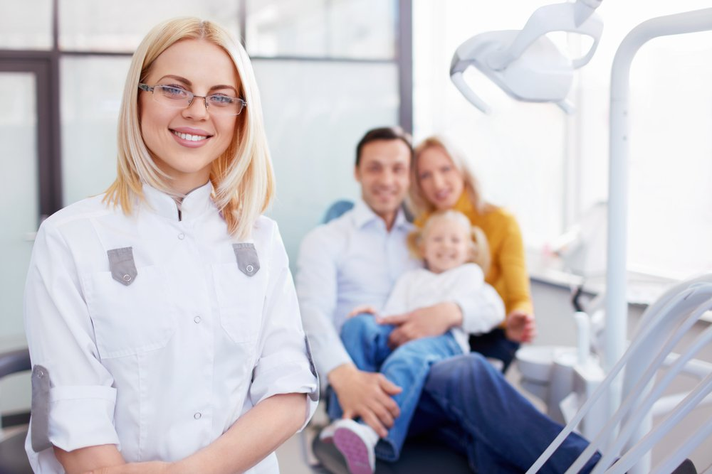 a young female orthodontist stands in her treatment room with a family of patients